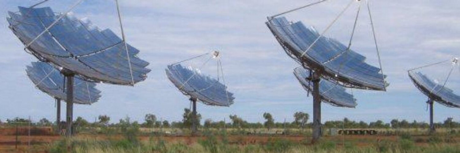 six dish shaped solar collectors in a field