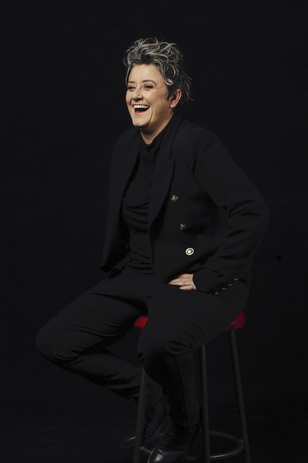 Chris Ryan, sitting on a stool dressed all in black with a black background, laughing