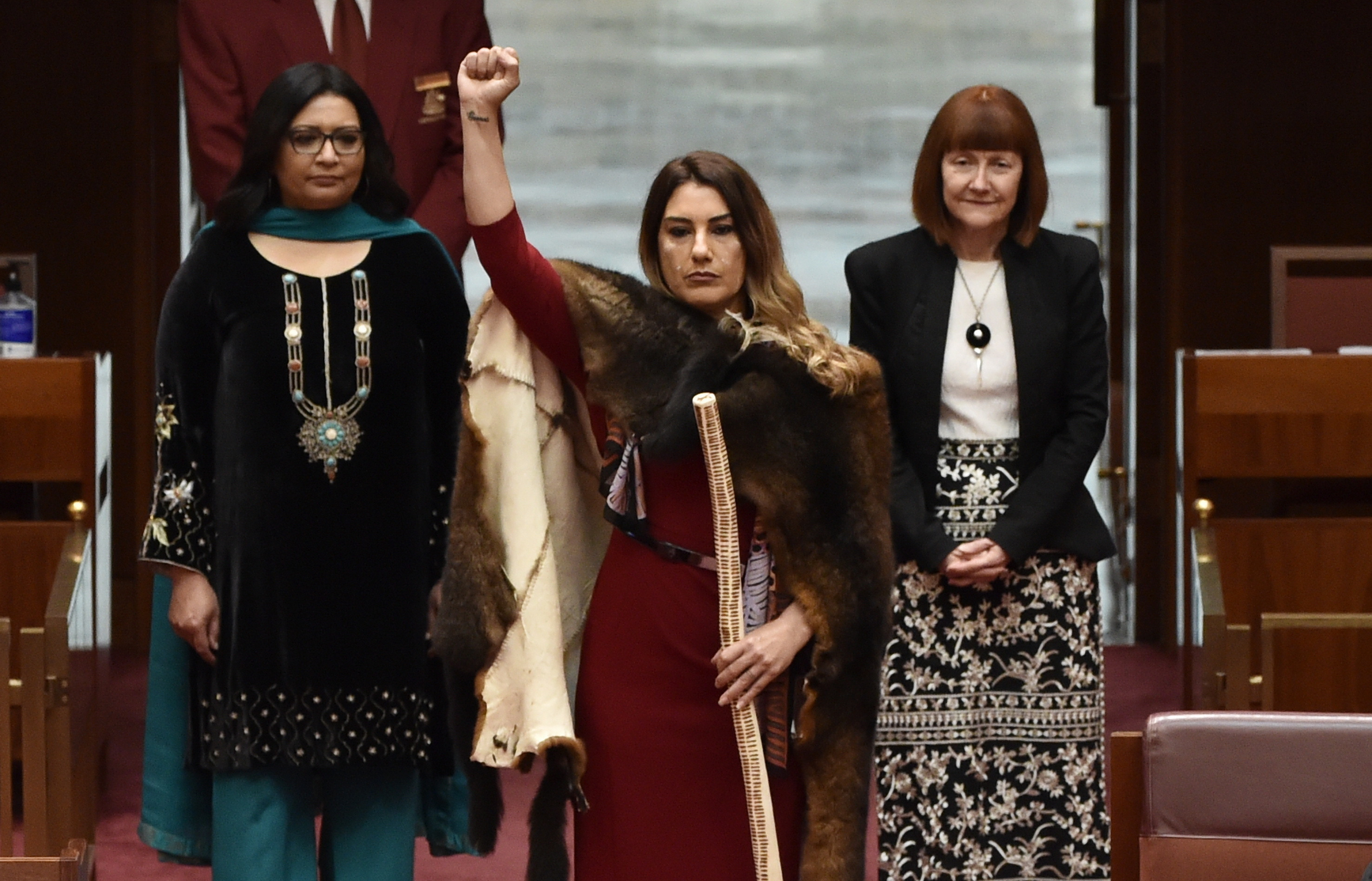 Lidia Thorpe enters the senate for the first time holding a message stick with one raised fist. Senators Mehreen Faruqi and Rachel Siewert stand alongside