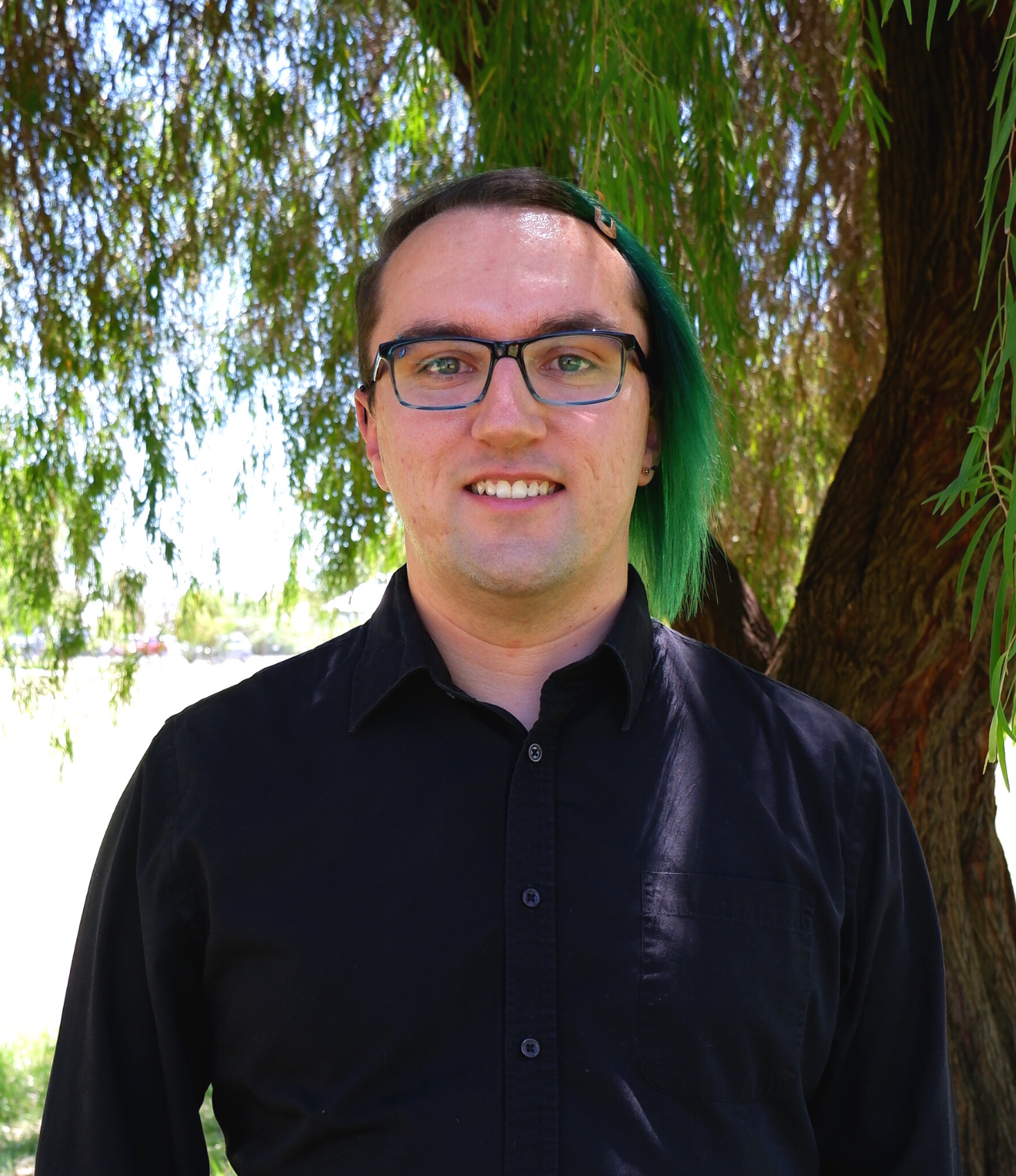 smiling young person with glasses and green hair parted to the right and clipped away from their face, wearing a black button down shirt with a willow tree in the background