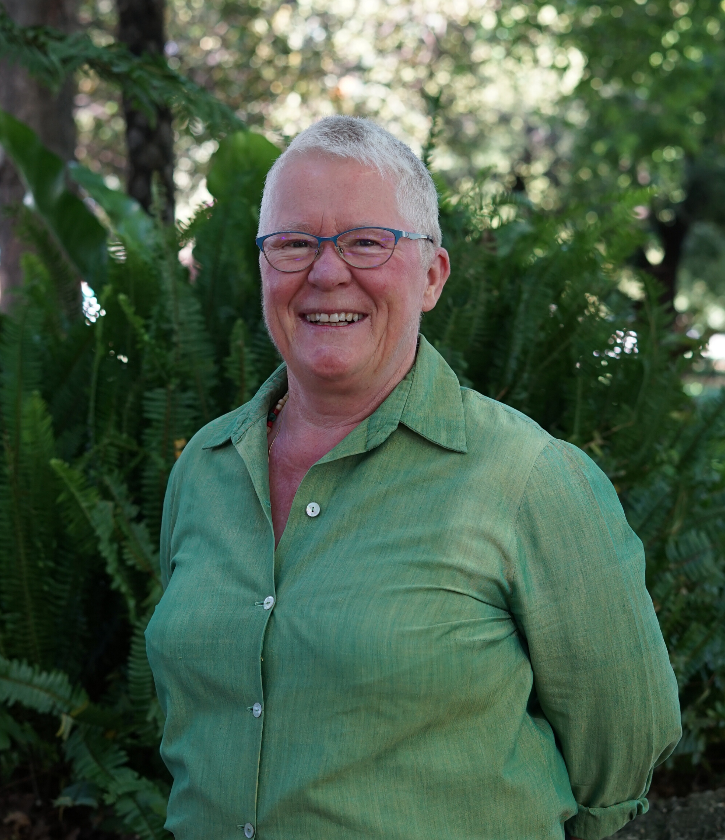 Smiling woman with short white hair and wire framed glasses, wearing a light green button down shirt with green foliage in background