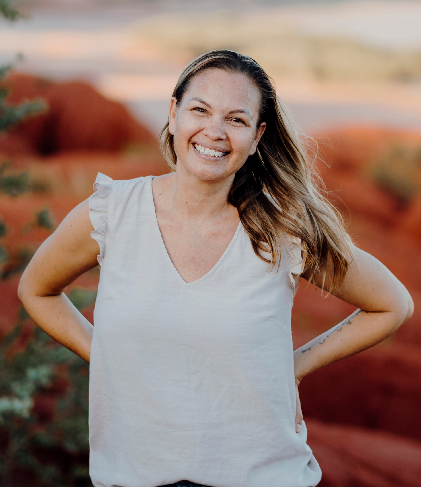 smiling woman with her hands on her hips wearing a white blouse with red rocks in the background