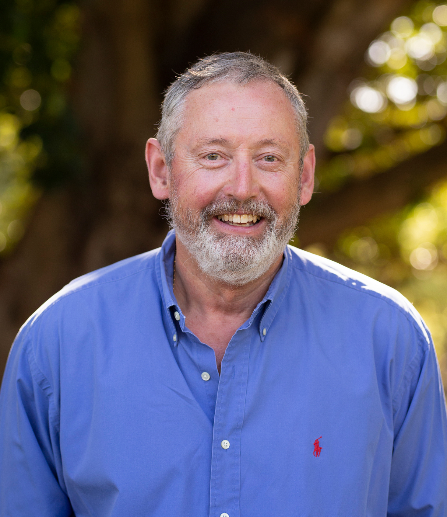 smiling older man with grey hair and a grey beard, wearing a blue button down shirt with green foliage in the background