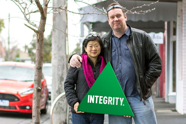 "A couple holding a triangle that says ""Integrity"""