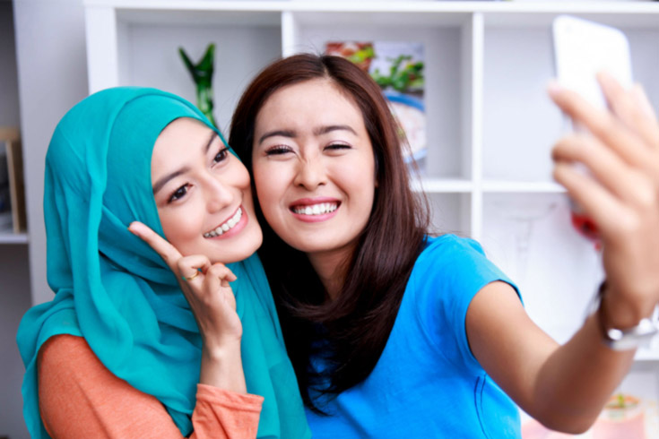 Two Asian women take a selfie, one wears a hijab, the other doesn't