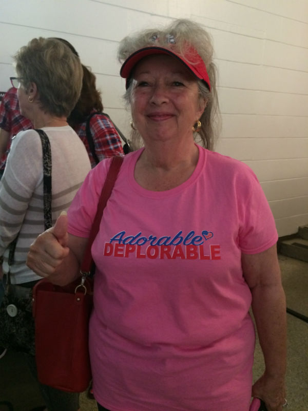 "Woman in pink t-shirt with ""adorable deplorable"" slogan smiling at camera"
