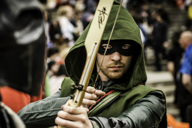 Man dressed as Arrow in green hood holding bow