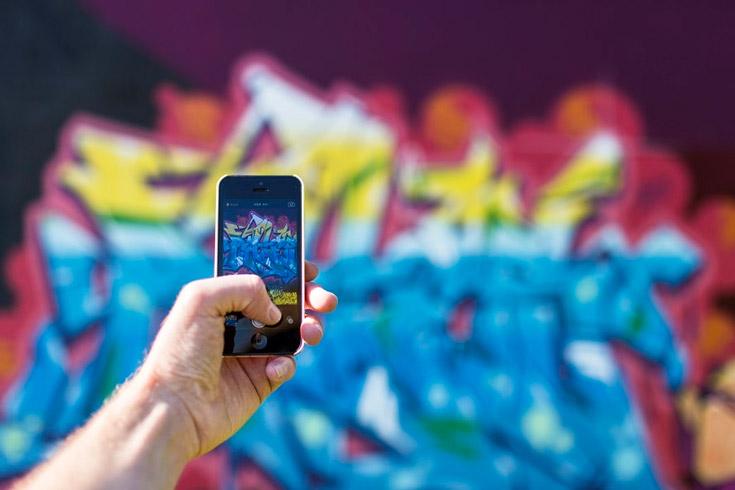 Man taking photo of graffiti