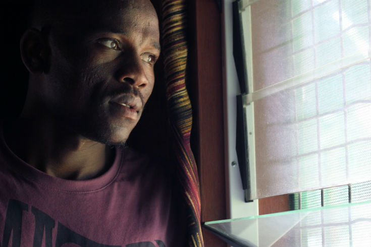 Aziz, a young man from Sudan, looking through a dirty and broken window. Image credit: Michael Green