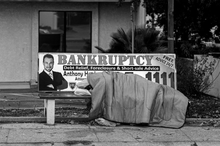 Person sleeping under a sleeping bag on a bench seat on the street. The bench seat has an ad for a bankruptcy lawyer on it.