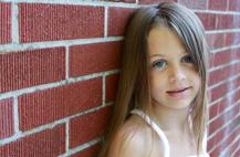 Girl standing against a brick wall. Image cc Jenn Durfey