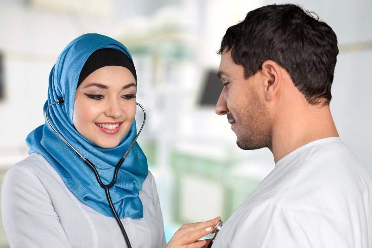 An image of a woman checking the heartrate of a patient