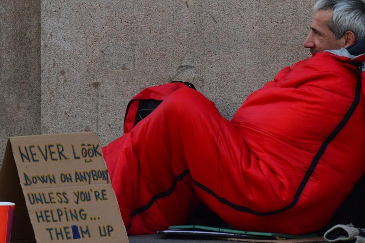 Homeless man with a sign: Never look down on anybody unless you're helping them up