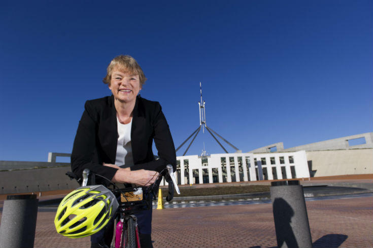 Senator Janet Rice with a bicycle in front of Parliament House in Canberra