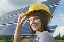 seitliches Kopf-und-Schulter-Porträt einer jungen, brünetten Frau mit gelben Bauhelm als Kopfbedeckung und optimistischen Blick in die Kamera; rechte Hand am Helm