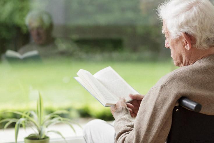 Older man reading near a window