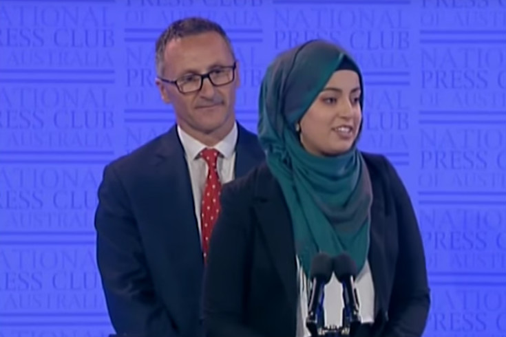 Senator Richard Di Natale standing behind Nada, a young woman in a green hijab, at the National Press Club podium