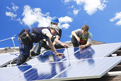 Image of three people on a roof installing solar panels