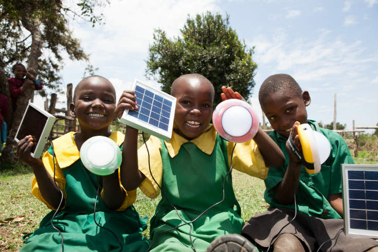 Children at a primary school in Kenya, smiling and holding solar powered lamps