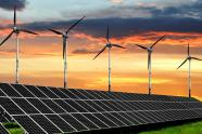solar panels and wind turbines at sunset