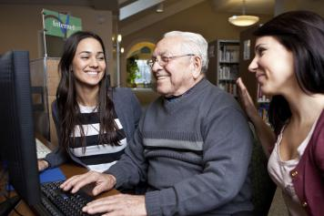 Image of young people with an older people at a computer