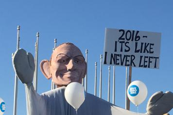 "photo of a large papier mache head of Tony Abbott holding a sign ""2016 — it's like I never left"""