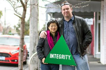 """A couple holding a triangle that says """"Integrity"""""""