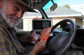 Robin Chapple in a car with flyers