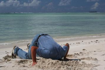 Man burying his head in the sand