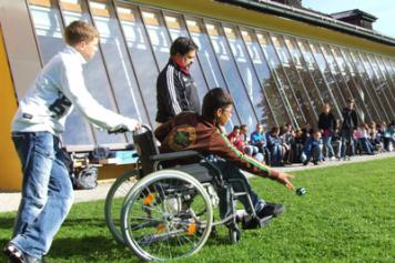 a teenaged boy in a wheelchair plays sport while classmates and a coach watch