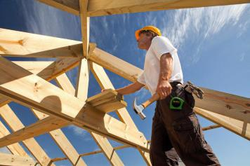 Image of a man building a timber-framed house