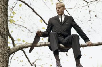 Getty Images: man sitting on a tree branch