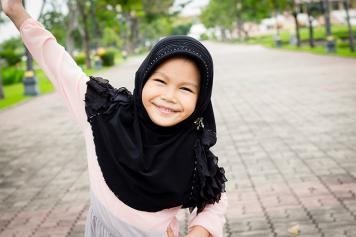 Image of a smiling girl wearing a headscarf