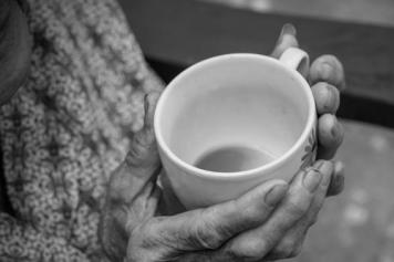 Old person's hands holding a cup
