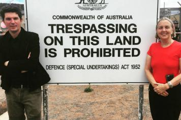 "Scott Ludlam and Lee Rhiannon standing next to a sign at Pine Gap saying ""Commonwealth of Australia - Trespassing on this land is Prohibited"""