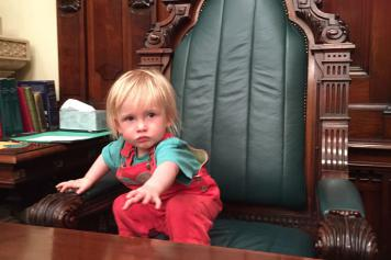 Image of a young child Tadgh in the Speaker's Chair of the SA Parliament after his same-sex parents won the right to both be on his birth certificate