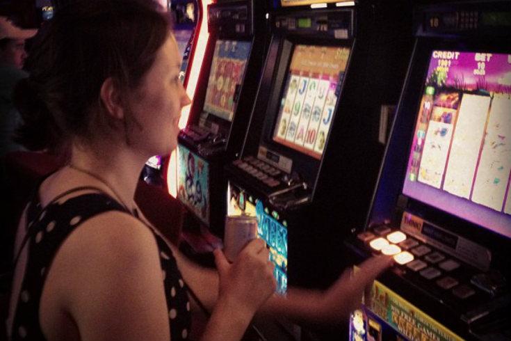 Woman playing electronic gambling machine (EGM)