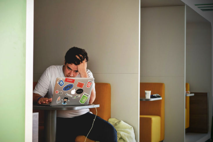 Young man looking at a laptop screen and looking stressed